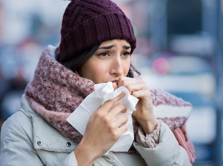 Jauna moteris, apsirengusi žieminiais drabužiais, kosi į servetėlę