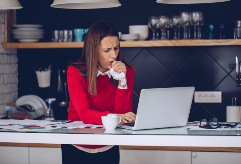 Kas sukelia kosulį? Moteris stovi virtuvėje, dirbdama prie nešiojamojo kompiuterio, ir kosi į servetėlę.