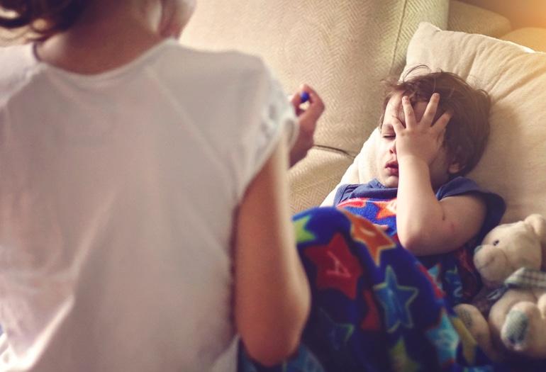 Susirgęs vaikas guli po antklode, susiėmęs už galvos, ir šlapiai kosi